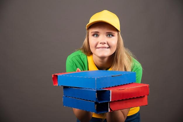 Sorridente fattorina in uniforme che tiene cartoni di pizza.