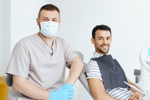 Улыбающийся стоматолог и пациент глядя портрет. хорошо оборудованный кабинет стоматологической клиники. стоматология, стоматология, ортодонтия