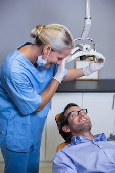 Улыбающийся ассистент стоматолога, регулирующий свет пациента