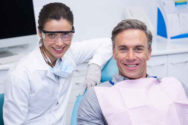 Улыбающийся стоматолог пациентом в медицинской клинике
