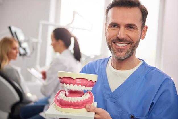 Улыбающийся стоматолог показывает искусственные протезы