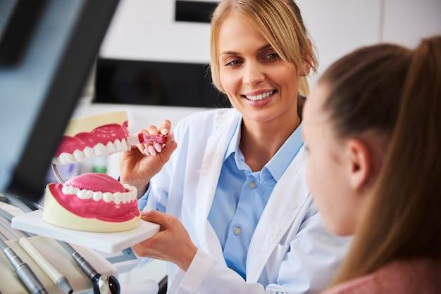 歯を磨く適切な方法を示す笑顔の歯科医