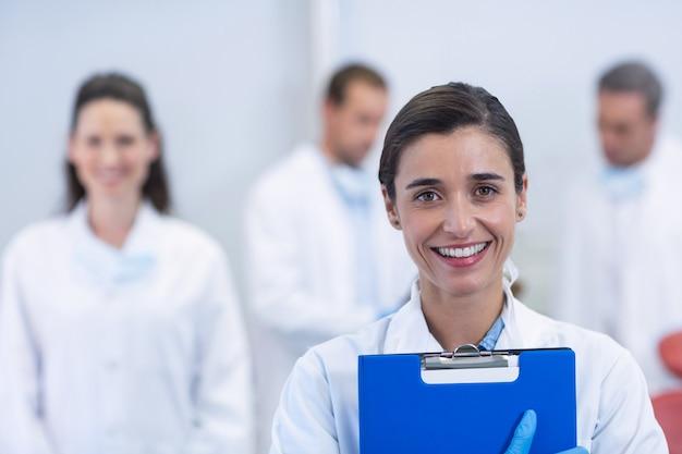 Улыбающийся стоматолог, стоящий в стоматологической клинике