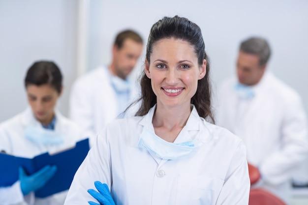 Улыбающийся стоматолог, стоящий со скрещенными руками