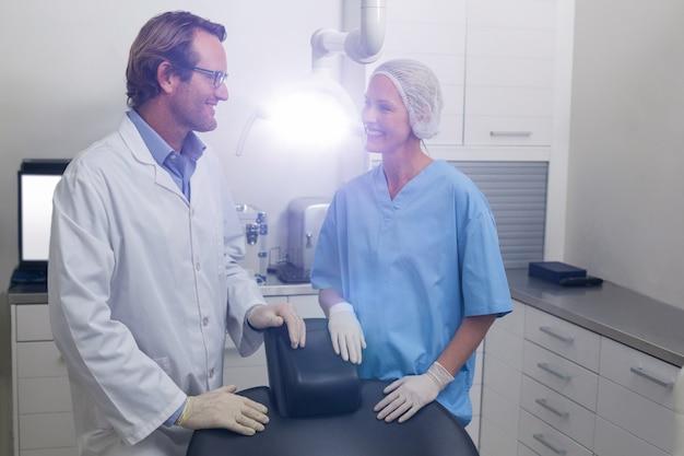 Улыбающийся стоматолог разговаривает с ассистентом стоматолога