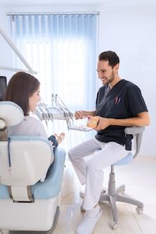 Smiling dentist using toothbrush on teeth model in dental clinic
