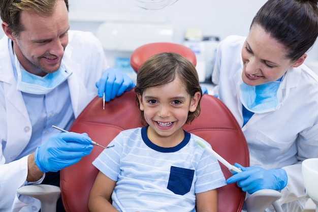 Smiling dentists examining young patient