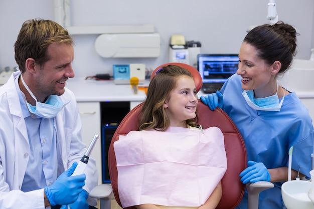 Улыбающиеся стоматологи, взаимодействующие с молодым пациентом