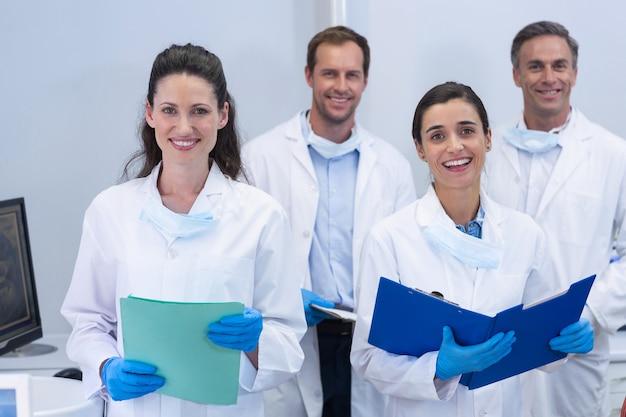Улыбающиеся стоматологи, стоя в стоматологической клинике