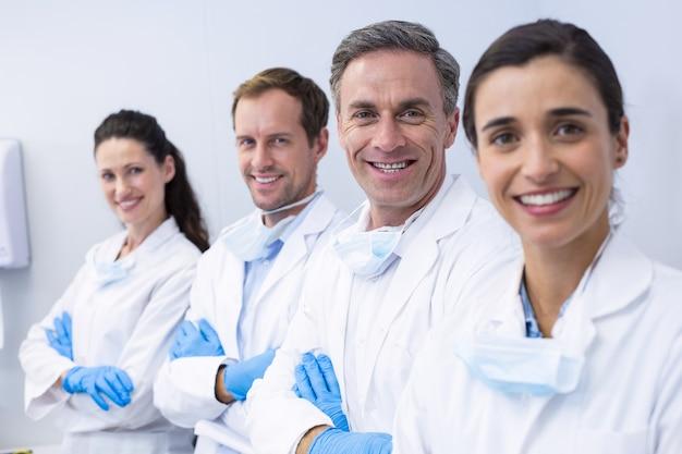Улыбающиеся стоматологи, стоя со скрещенными руками