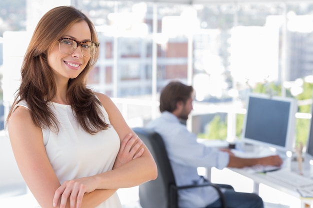 Smiling desginer standing in her office wearing glasses