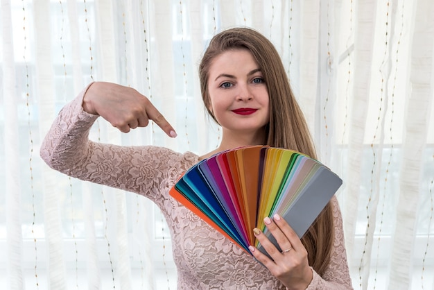 彼女の手で色見本を示す笑顔のデザイナー