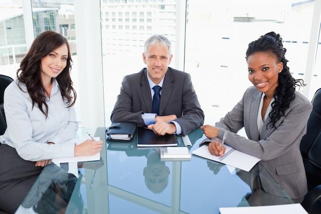 2人の従業員の間の窓の前の机に座っている笑顔のディレクター