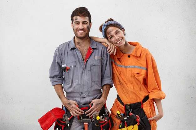 Smiling dirty woman leans on shoulder of man mechanic, helps him to repair car on work station