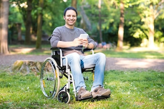 Smiling disabled man using a tablet in a park
