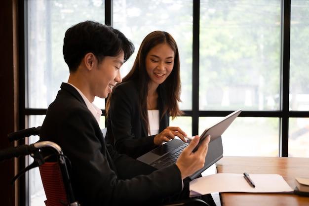 현대 사무실에서 동료와 함께 앉아 웃는 장애인 노동자.