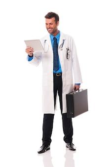 Улыбающийся врач что-то проверяет на цифровом планшете