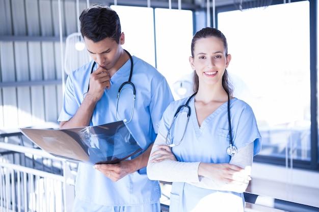 病院で彼の同僚とax線レポートを調べる医師の笑みを浮かべてください。