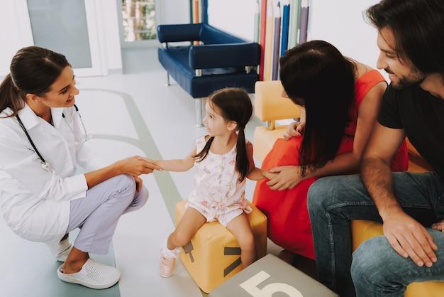 Smiling doctor handshaking kid stress relief.
