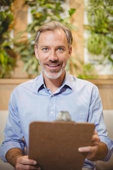 クリニックでクリップボードを保持している医者の笑みを浮かべてください。