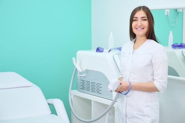 レーザー脱毛の美容院で白衣を着て笑顔の医者とカメラを見て