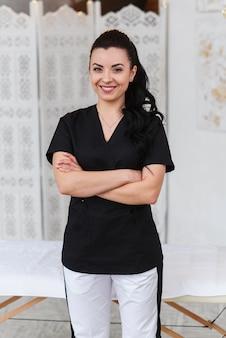 カメラ目線と近代的な診療所のマッサージテーブルの後ろに立っている笑顔の医者。ヘルスケアと医療の概念。