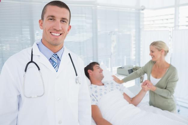 뒤에 그의 환자와 함께 카메라를보고 웃는 의사