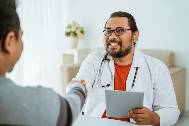 Smiling doctor shaking hand with patient in his office