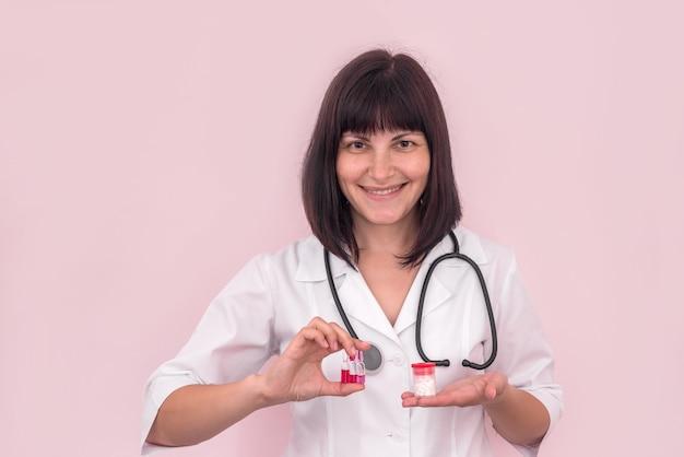 容器にアンプルと錠剤を示す笑顔の医者