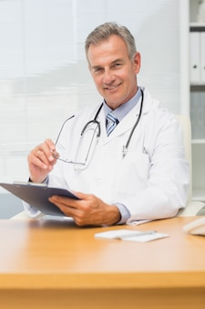 Smiling doctor sitting at his desk with clipboard