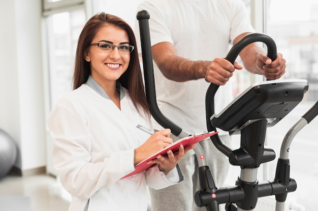 Smiling doctor sitting next to patient working out