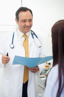 Smiling doctor talking to his patient
