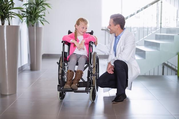 女の子を無効にするために話している笑顔の医者