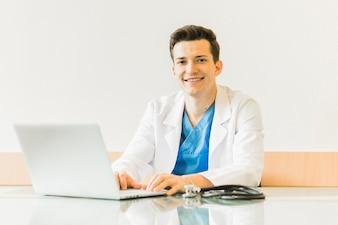 Smiling doctor using laptop