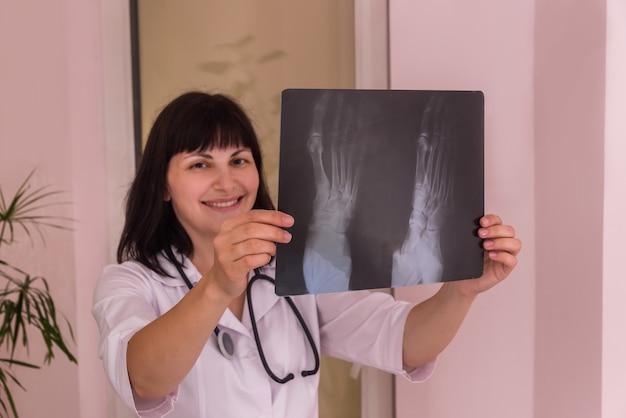손에 환자의 엑스레이와 웃는 의사 프리미엄 사진