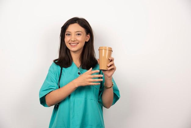 Medico sorridente con lo stetoscopio che tiene tazza di caffè su priorità bassa bianca. foto di alta qualità