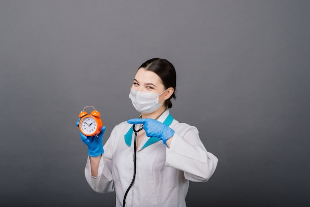 Улыбающаяся женщина-врач в маске, указывающая на часы, время вакцины