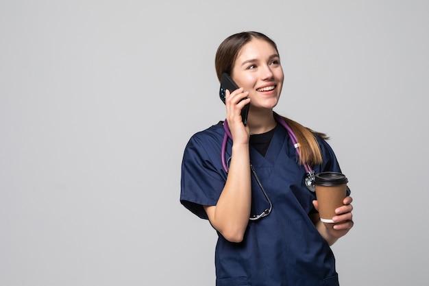 白で隔離の携帯電話を話している医者の女性の笑顔