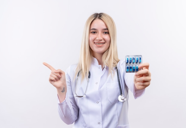 청진 기 및 의료 가운을 입고 웃는 의사 젊은 금발 소녀 격리 된 흰색 배경에 측면에 환 약을 들고 치과 중괄호 포인트