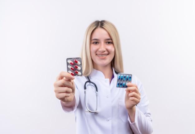 孤立した白い背景に両手で丸薬を保持している歯科用ブレースで聴診器と医療用ガウンを身に着けている医師の若いブロンドの女の子の笑顔