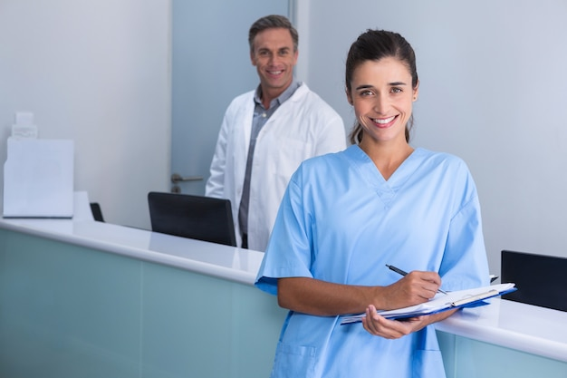 Smiling doctors standing against wall at clinic