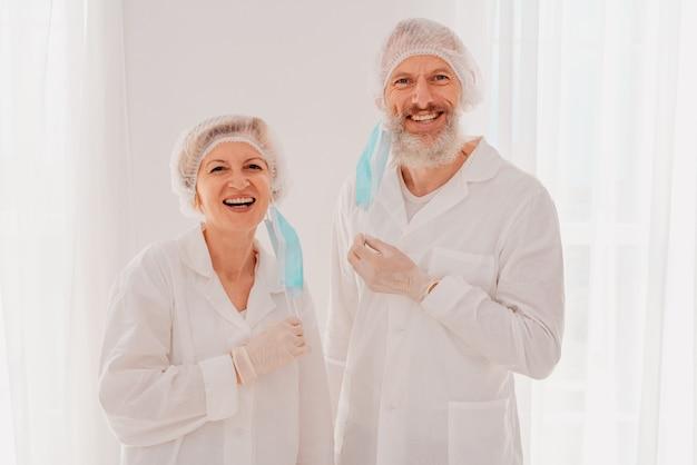 안면 마스크를 쓴 웃는 의사들은 코로나 19 퇴치에 기뻐합니다