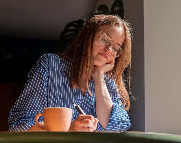 Улыбающаяся мечтающая женщина пишет планы в блокноте, сидя за деревянным столом в кафе с чашкой кофе и ...