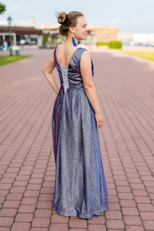 Smiling dreamy caucasian woman in amethystine floor-length dress turned her back on pavement.