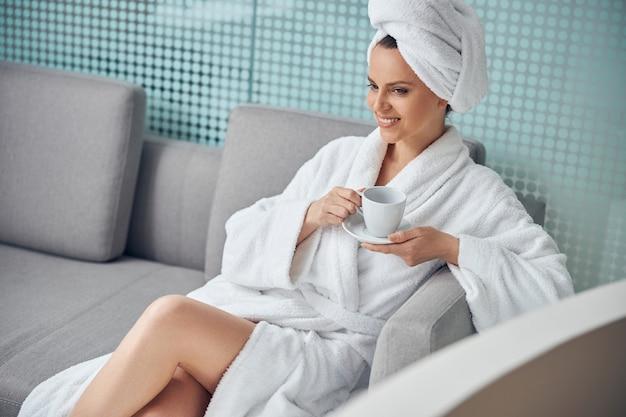 웰빙 센터에서 소파에 차 한잔과 함께 편안한 꿈꾸는 아가씨 미소