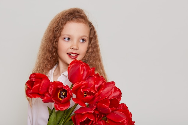 Smiling dreamy schoolgirl with big bouquet of beautiful flowers looking away with happy expression