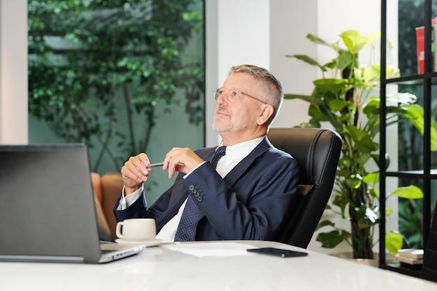 Улыбающийся мечтательный старший бизнесмен сидит за офисным столом и обдумывает идеи для развития бизнеса