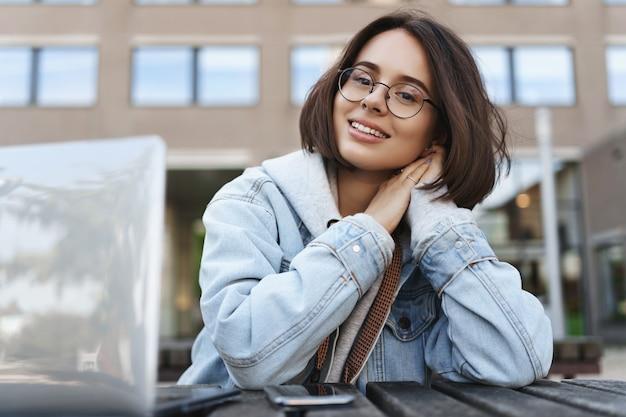 Улыбающаяся мечтательная молодая женщина в очках, смотрящая в камеру, счастлива, расслабляясь, разговаривая с одноклассником во время обеденного перерыва в университетском городке, используя ноутбук, готовит эссе.