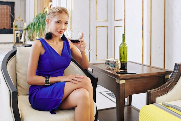 Smiling dressed up young vietnamese woman drinking red wine when sitting at table in hotel lobby