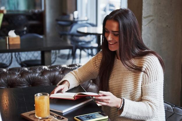 プロセス中に笑顔。テーブルと黄色のドリンクを飲みながらレストランに座って、新しい興味深い情報を読んで受け取る時間